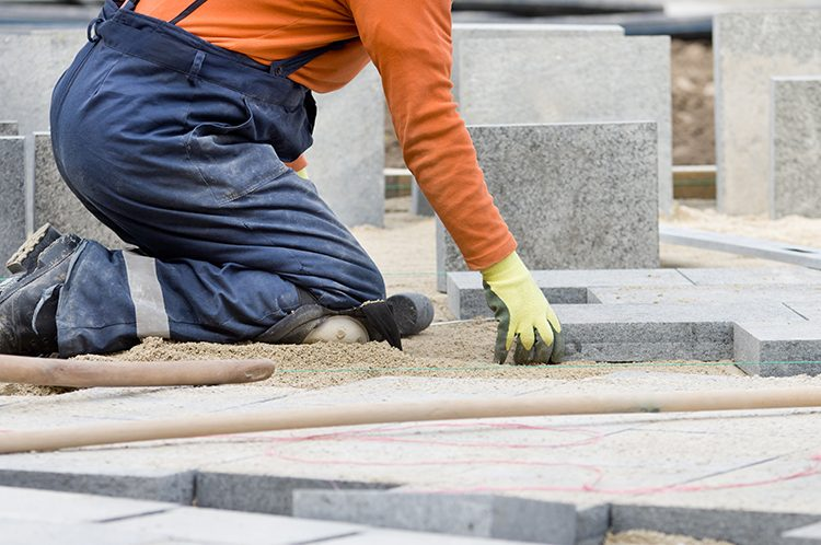 Construction worker on knees placing stone tiles in sand for pavement