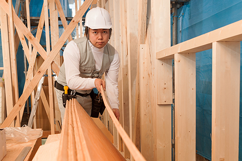 Japanese carpenter working at the construction site of the wooden house.