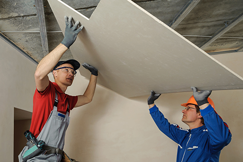 Drywall Installers. Men holding a gypsum board figured cut