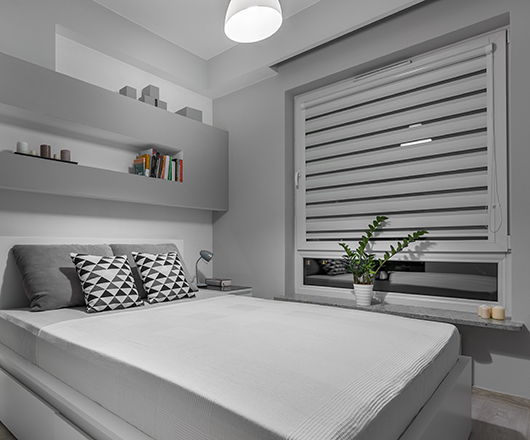 Comfortable double bed in modern and simple grey bedroom